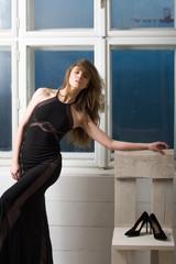 Pretty girl in black dress posing at white chair