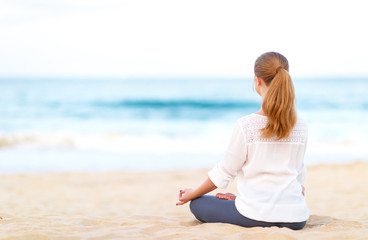 Fototapete - woman practices yoga and meditates in lotus position on beach.