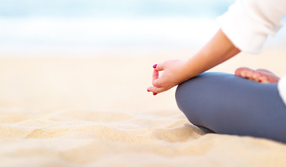 Fototapete - hand of woman practices yoga and meditates on beach.