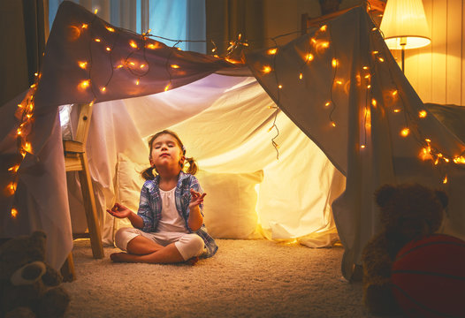 child girl playing meditates in yoga pose in tent at home