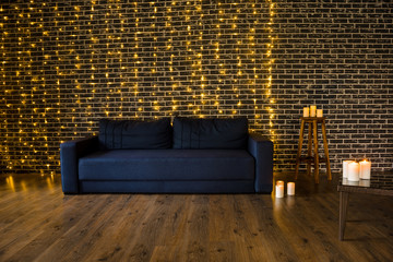 Dark blue sofa in dark loft interior decoration candles and lamps