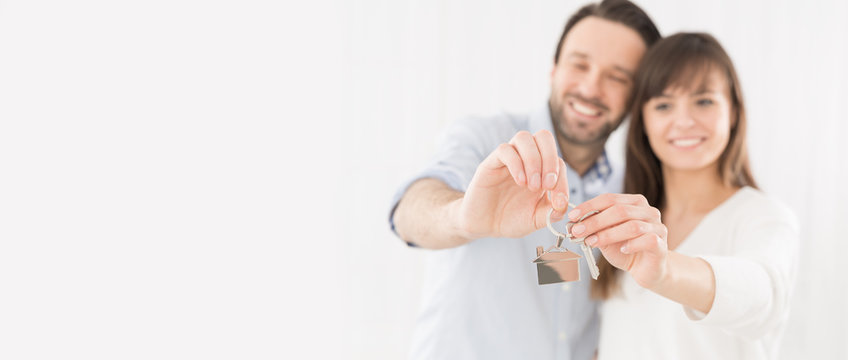 A young couple holding hands house key.