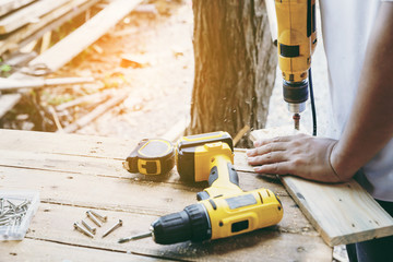 Carpenter's screwing a wood plate by wireless drill for make a chair, Diy at Home concept
