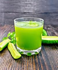 Juice cucumber in glassful on dark board