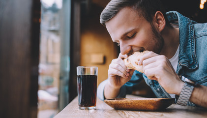 Young man sitting in a restaurant and eating a hamburger
