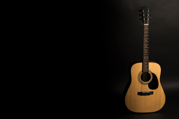 Acoustic guitar on a black background on the right side of the frame. Stringed instrument. Horizontal frame.