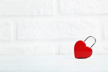 Heart shaped padlock on brick wall background