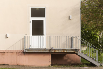 House wall with door and upstairs staircase