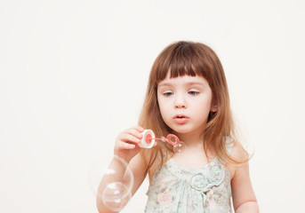 Girl blows soap bubbles on monophonic background