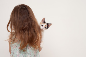 Girl standing with her back and holding a kitten