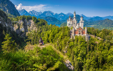 Neuschwanstein Castle with young man sitting on a cliff enjoying the spectacular view in summer, Füssen, Bavaria, Germany