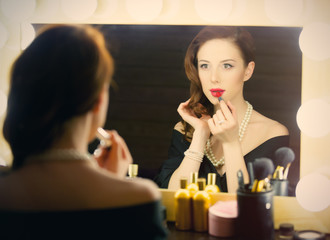 portrait of beautiful young woman using lipstick and looking at herself in the mirror