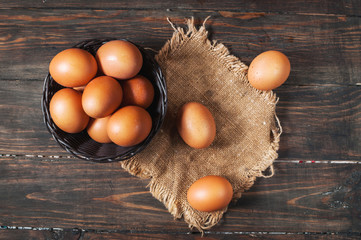 Farm Fresh Brown Chicken Hen Eggs in a Basket on Rustic Wood Counter Background