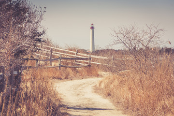 Beach walking path leading to lighthouse in vintage setting