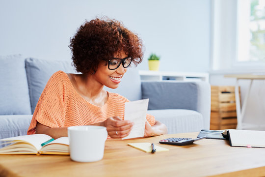 Young woman calcualting home finances, paying bills