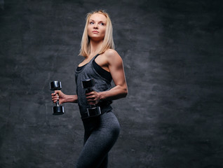 A sporty blond female dressed in a grey sportswear holds dumbbells.