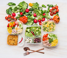 Healthy food concept. Variety of clean dieting salad bowls and vegetables with cutlery on white wooden background, top view, copy space. Various fresh vegetable salads in  plastic package .