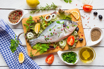 Uncooked fish with herbs, lemon and spices on wooden cutting board