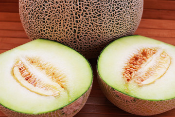 Melon fruit is spherical, has a rough texture and delicious sweet taste is cut on  brown background