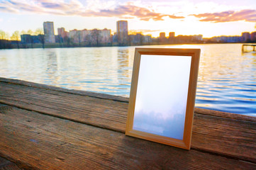 Wooden photo frame on the background of the lake at sunset