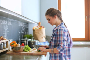 Young woman cutting vegetables in kitchen near desk