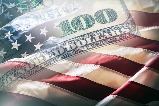 USA flag and American dollars. American flag blowing in the  wind and 100 dollars banknotes in the background.