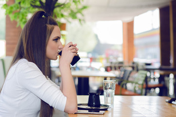 Girl sits on the side and enjoy your morning coffee at the coffee shop