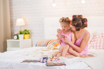 Mom and daughter in the bedroom on the bed in the curlers make up
