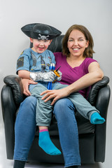 Mother and cute child dressed in pirate and police costume sitting on mother´s knee in black armchair. Mother and son looking at camera.