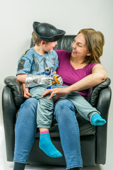 Mother and cute child dressed in pirate and police costume sitting on mother´s knee in black armchair. Mother and son looking at each other.