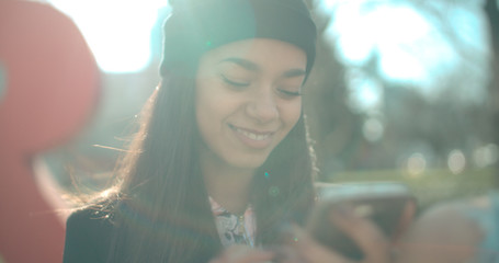 Portrait of young African American woman using phone, outdoors.