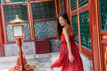 Wall Mural - Beautiful asian model smiling laughing healthy living. Happiness and joy lifestyle. Chinese woman in elegant red silk dress dancing and running in china travel.