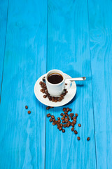 Coffee cup with espresso on blue wooden background