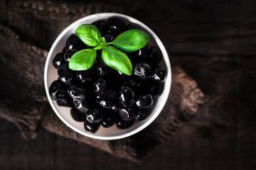 Black olives  on a white  plate on dark wooden board, top view with copyspace.