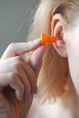 Blonde girl puts hand earplugs in ear closeup on white background