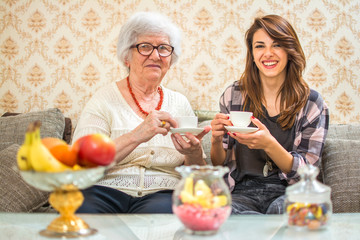 Grandmother enjoying coffee cup with her granddaughter at home.