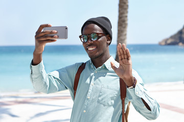 People, lifestyle, travel, tourism and modern technology. Attractive black traveler in stylish shades and headwear posing for selfie with happy smile and hello gesture against blue sea background