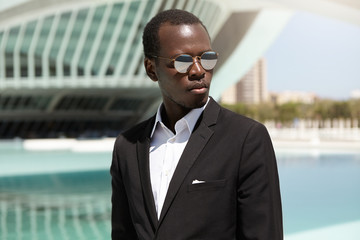 Portrait of attractive successful African entrepreneur wearing black suit and round sunglasses having serious confident look, standing outdoors in urban scenery with modern buildings in background