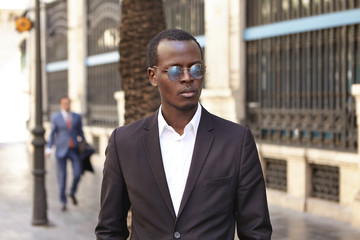 Urban outdoor portrait of confident serious young dark-skinned entrepreneur wearing stylish round shades and formal suit standing on street against office building background, waiting for cab