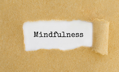 Text Mindfulness appearing behind ripped brown paper.