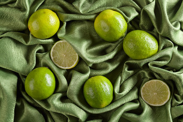 Group of whole and cut fresh limes on green satin