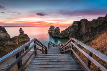 Wooden footbridge walkway to beautiful beach Praia do Camilo on coast of Algarve region, Portugal Wall mural