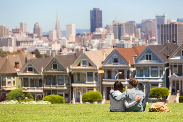 San Francisco tourist attraction at Alamo Square, the Painted Ladies famous postcard row, California travel. Couple tourists relaxing in grass enjoying popular destination. People lifestyle