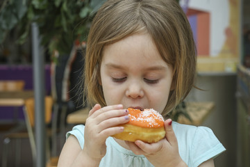 A small child bites a sweet donut. A child is a girl 4-5 years old.