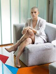 Mulher branca de cabelos raspados sentada no sofá