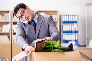 Young businessman moving offices after being made redundant