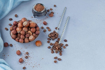 Hazelnut, coffee beans and cocoa powder in light blue background.