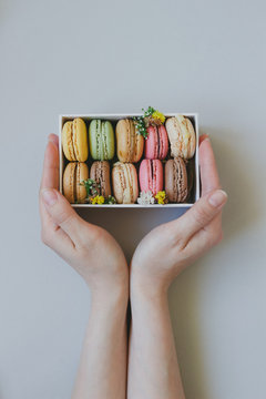 Hands holding gift box with delicious macaroons on the light blue background, top view