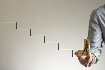 Wooden blocks with shape of man walking up stairs