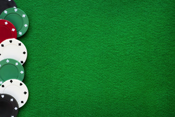 Poker chips on green felt casino table. Gambling, poker, blackjack and roulette theme